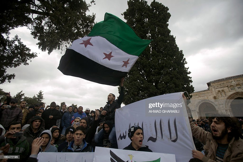 Palestinian protesters shout slogans against the Syrian regime while waving a pre-Baath Syrian flag, now used by the Free Syrian Army, during a demonstration after the Friday prayers at Al-Aqsa mosque compound in Jerusalem's old city on February 1, 2013. According to the UN, more than 60,000 people have been killed in the Syrian unrest that started with peaceful protests in March 2011 before turning into an armed revolt, faced with a brutal crackdown which has cost dozens of lives each day. AFP PHOTO/AHMAD GHARABLI