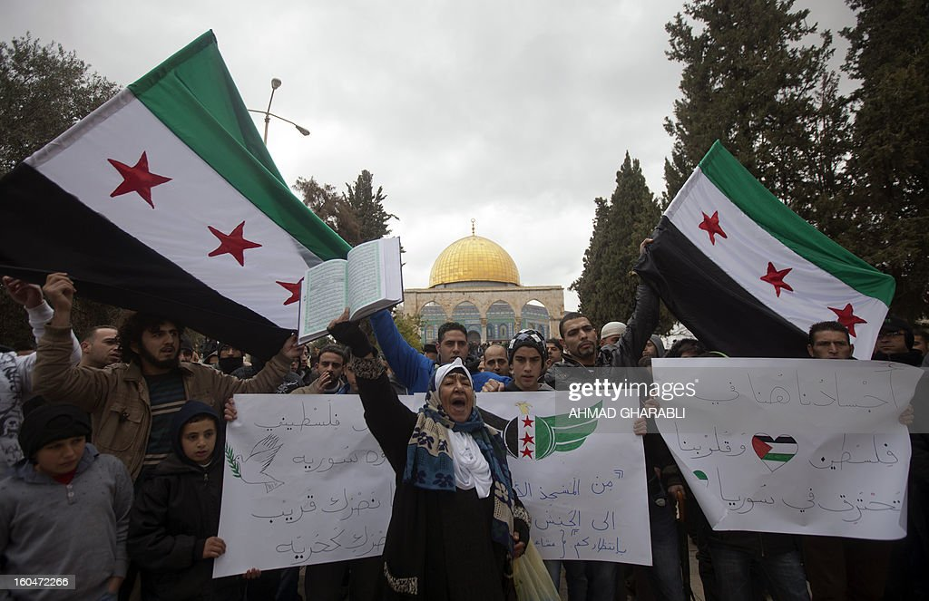 Palestinian protesters shout slogans against the Syrian regime while waving pre-Baath Syrian flags, now used by the Free Syrian Army, during a demonstration after the Friday prayers at Al-Aqsa mosque compound in Jerusalem's old city on February 1, 2013. According to the UN, more than 60,000 people have been killed in the Syrian unrest that started with peaceful protests in March 2011 before turning into an armed revolt, faced with a brutal crackdown which has cost dozens of lives each day. A sign (R) reads in Arabic 'Our bodies are in Jerusalem while our hearts burn in Syria'.