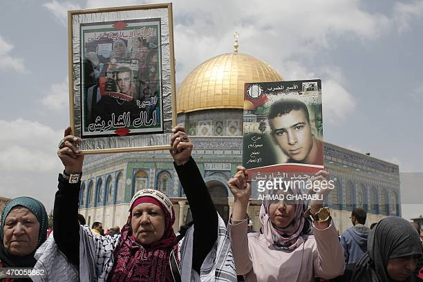 Palestinian protesters shout slogans and hold portraits of relatives incarcerated in Israeli jails during a rally marking Palestinian Prisoner Day...