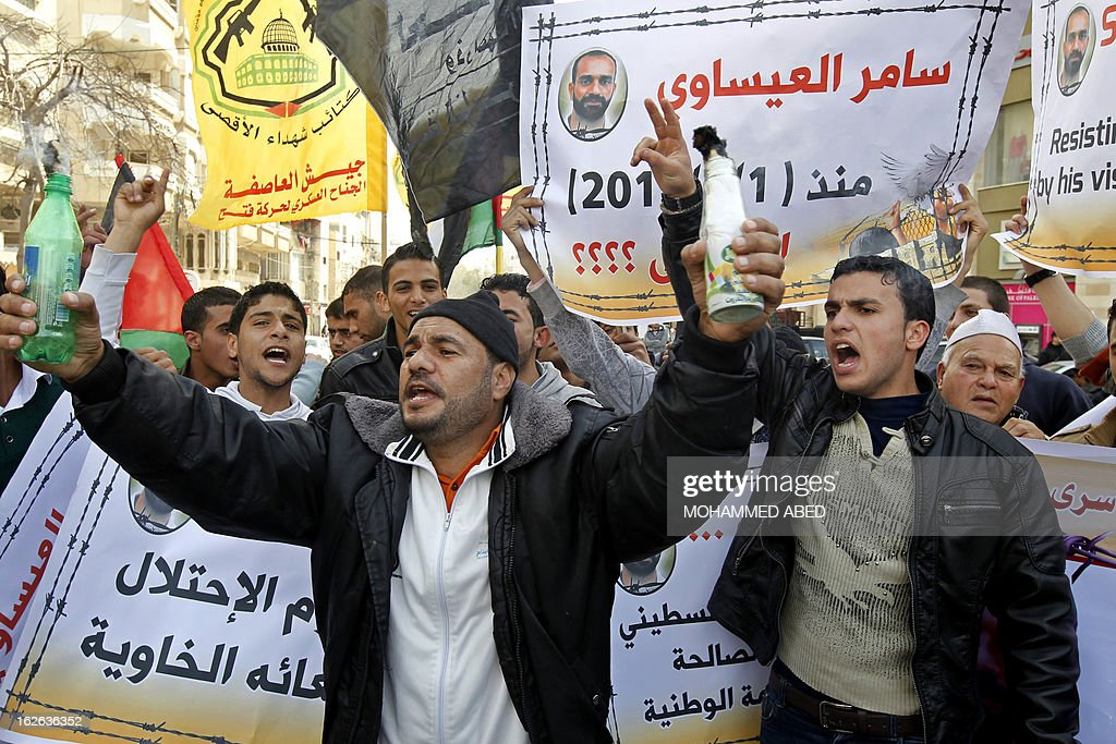 Palestinian protesters shout slogans during a demonstration in Gaza City in solidarity with Palestinian prisoners held in Israeli jails on February 25, 2013. Protests in support of Palestinian prisoners on hunger strike in Israeli prisons have been building and gained new momentum with the sudden death in his cell of 30-year-old Arafat Jaradat.