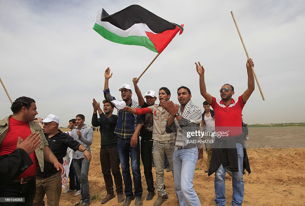 Palestinian protesters shout slogans during a rally marking Land Day near the southern Gaza Strip's border with Israel, east of Rafah, on March 30, 2013. Land Day commemorates the death of six Arab Israeli protesters at the hands of Israeli troops during mass protests in 1976 against plans to confiscate land in Galilee.