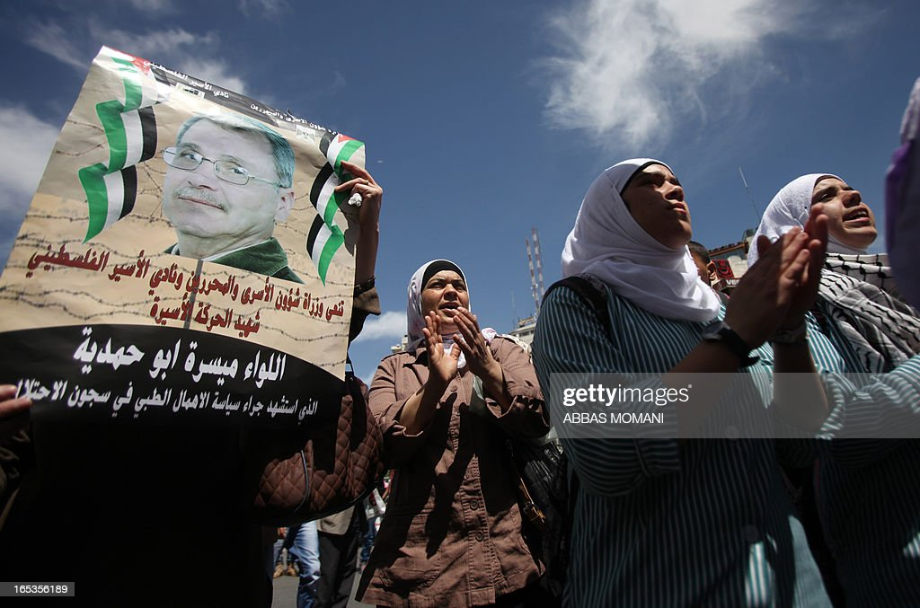 Palestinian protesters shout slogans while holding a poster of Maisara Abu Hamdiyeh, a Palestinian prisoner who died of cancer while in Israeli detention, during a demonstration against his death in the West Bank city of Ramallah on April 3, 2013. Abu Hamdiyeh, who had served 10 years of a life sentence for attempted murder, died in an Israeli hospital two months after being diagnosed with throat cancer. The Palestinian leadership has accused Israel of medical negligence with news of his death sparking angry clashes.