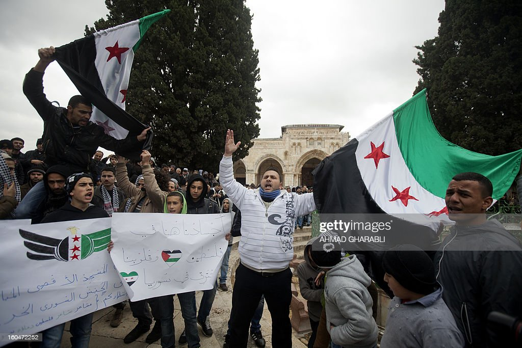 Palestinian protesters shout slogans while waving pre-Baath Syrian flags, now used by the Free Syrian Army, during a demonstration after the Friday prayers at Al-Aqsa mosque compound in Jerusalem's old city on February 1, 2013. According to the UN, more than 60,000 people have been killed in the Syrian unrest that started with peaceful protests in March 2011 before turning into an armed revolt, faced with a brutal crackdown which has cost dozens of lives each day. A sign (C) reads in Arabic 'Our bodies are in Jerusalem while our hearts burn in Syria'. AFP PHOTO/AHMAD GHARABLI
