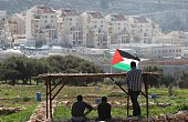 Palestinian protesters sit under a shelter flying their national flag as they look out at the Israeli settlement of Modiin Illit during a...