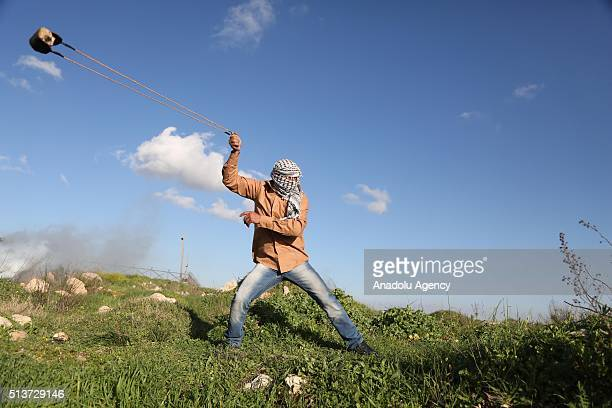 Palestinian protesters sling stones to Israeli security forces during a protest against Israeli violations in West Bank and Damascus in front of Ofer...