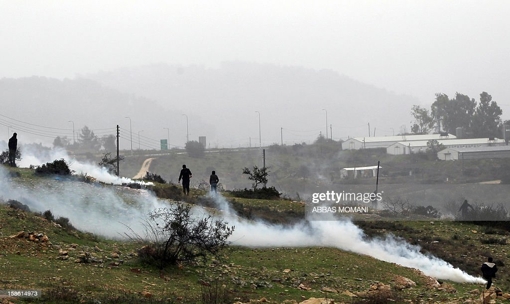 Palestinian protesters stand amid a fog of tear gas fired by Israeli security forces as clashes erupted following a march organized by inhabitants of the West Bank village Nabi Saleh on December 21, 2012, to protest against the expansion of Jewish settlements on Palestinian land.