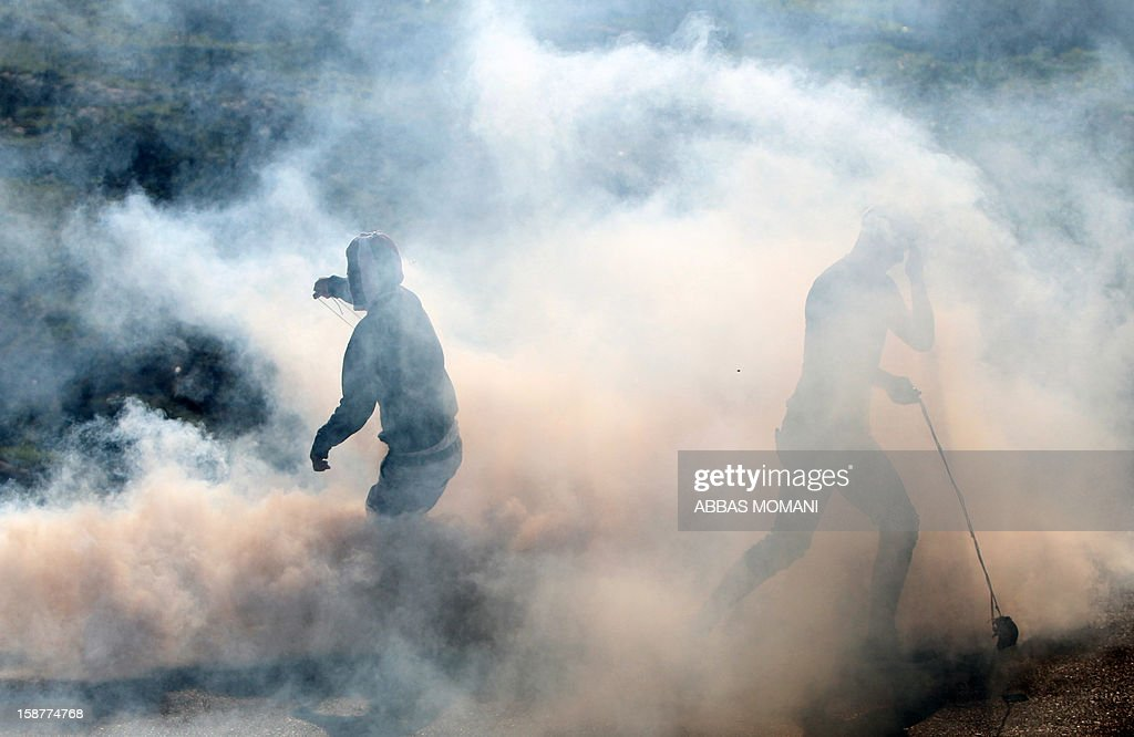 Palestinian protesters stand amid a fog of tear gas fired by Israeli security forces during clashes that erupted following a march organised by residents of the West Bank village Nabi Saleh to protest against the expansion of Jewish settlements on Palestinian land on December 28, 2012.