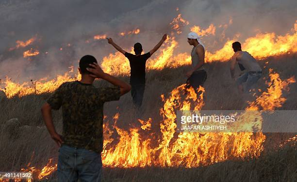 Palestinian protesters stand amid blazes of fire during clashes with Israeli settlers in the West Bank village of Burin on October 3 2015 Sporadic...