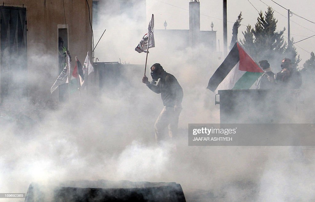 Palestinian protesters stand amidst tear gas smoke fired by Israeli forces during a protest against the expropriation of Palestinian land by Israel on January 18, 2013 in the village of Kafr Qaddum, near Nablus, in the occupied West Bank.