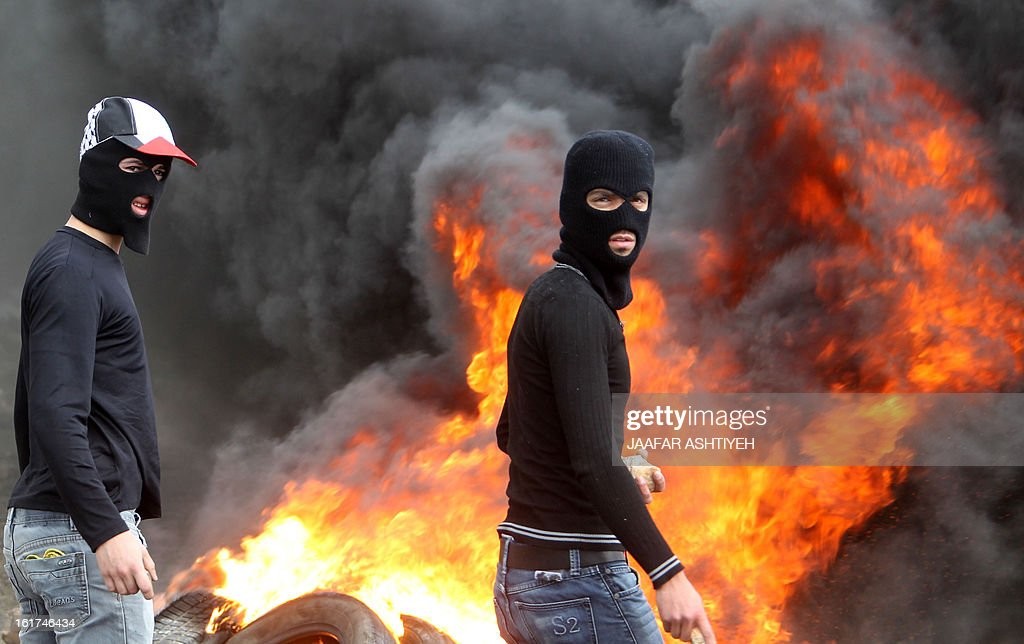 Palestinian protesters standing near burning tyres, gather stones to throw towards Israeli soldiers during clashes following a demonstration against the expropriation of Palestinian land by Israel on February 15, 2013, in the village of Kafr Qaddum, near the occupied West Bank city of Nablus.