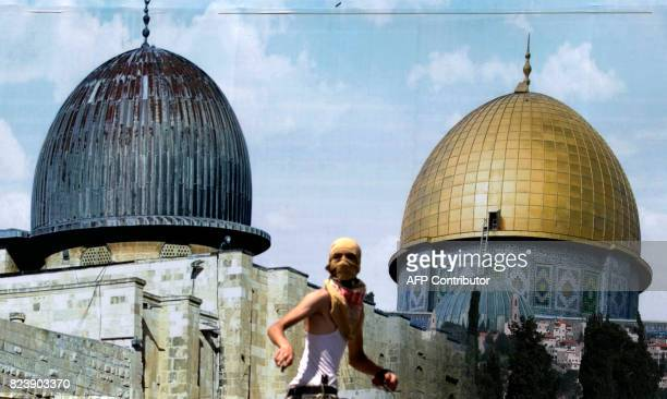 Palestinian protesters stands in front of a mural covered in an image of the Dome of the Rock during clashes between demonstrators and Israeli...