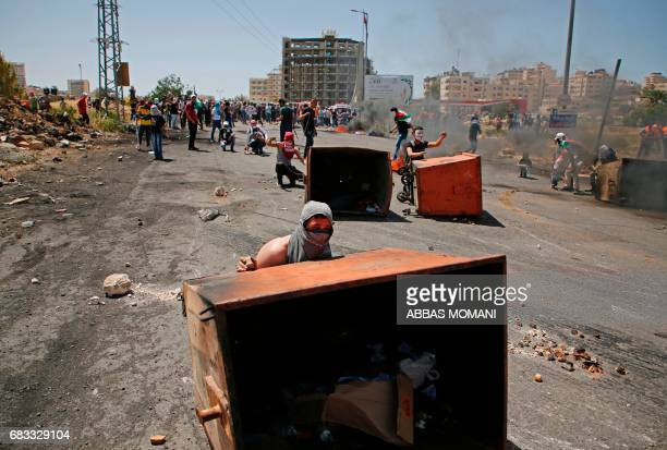 Palestinian protesters take cover behind rubbish bins during clashes with Israeli security forces following a protest marking the 69th anniversary of...