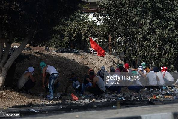 Palestinian protesters take cover during clashes at the Israeli Hawara checkpoint near the West Bank city of Nablus October 12 2015 Four Israelis and...