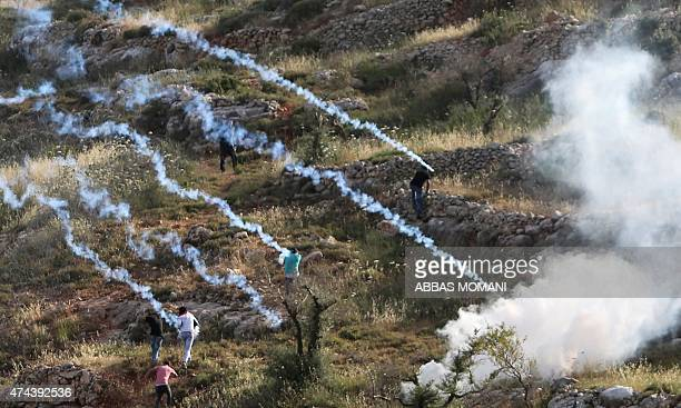 Palestinian protesters take cover from tear gas canisters fired by members of the Israeli security forces during clashes outside the compound of the...