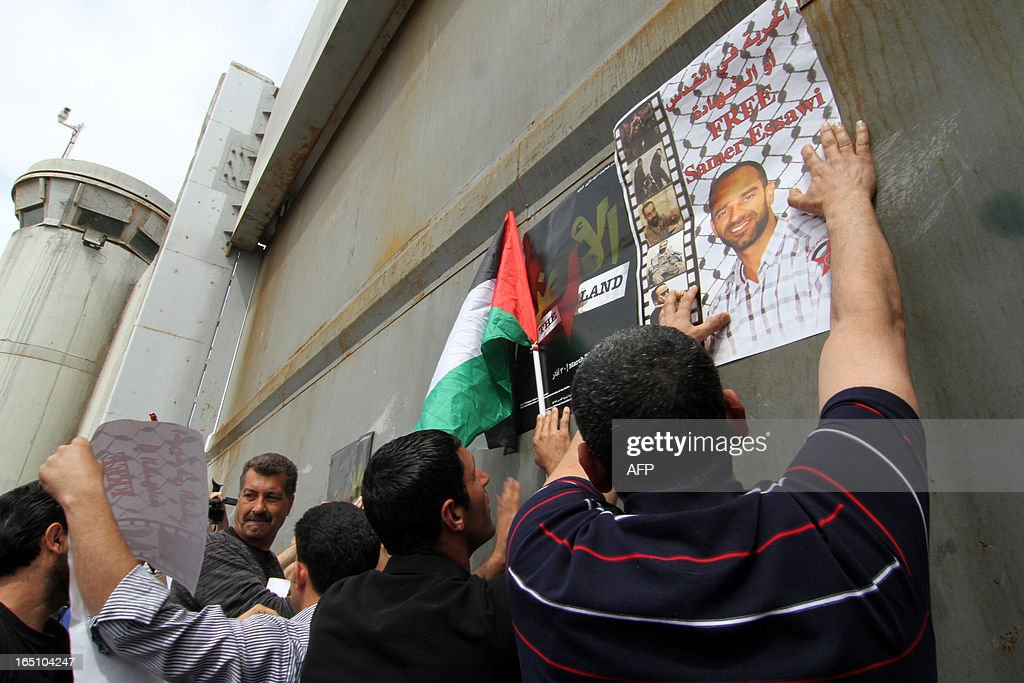 Palestinian protesters take part in a rally marking Land Day next to Israel's controversial separation barrier at the main entrance of the West Bank town of Bethlehem on March 30, 2013. Land Day commemorates the death of six Arab Israeli protesters at the hands of Israeli troops during mass protests in 1976 against plans to confiscate land in Galilee.