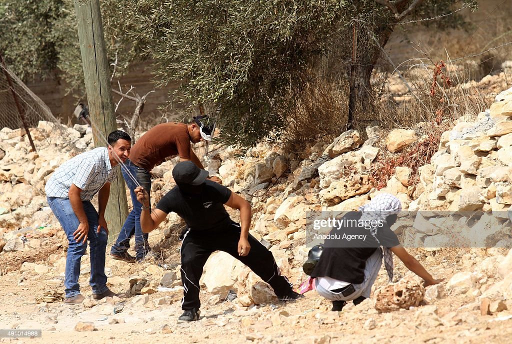 Palestinian protesters throw stones as a response to the Israeli forces attack during a demonstration after the Friday Prayer against Israeli...