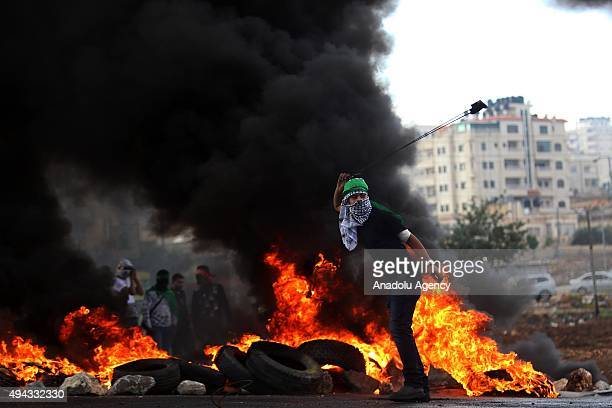Palestinian protesters throw stones as a response to the Israeli forces attack during a demonstration against Israeli Government's violations over...