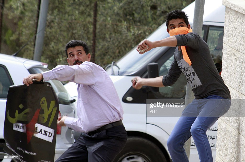 Palestinian protesters throw stones at an Israeli military tower along Israel's controversial separation barrier during a rally marking Land Day at the main entrance of the West Bank town of Bethlehem on March 30, 2013. Land Day commemorates the death of six Arab Israeli protesters at the hands of Israeli troops during mass protests in 1976 against plans to confiscate land in Galilee.
