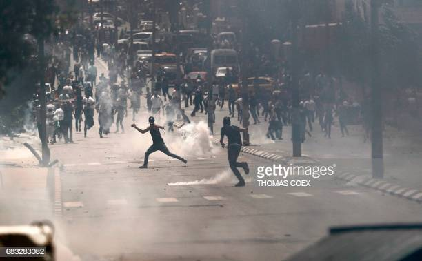 TOPSHOT Palestinian protesters throw stones at Israeli security forces during clashes as they demonstrate to mark the 69th anniversary of the 'Nakba'...