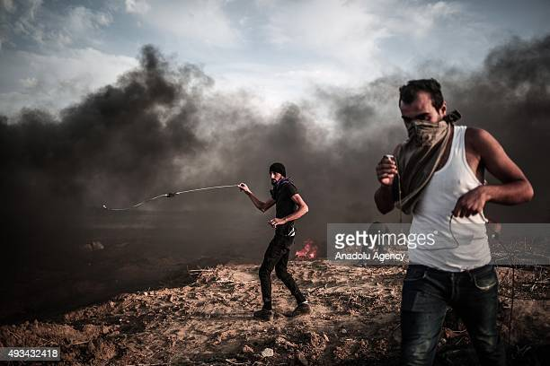Palestinian protesters throw stones at Israeli soldiers during a demonstration against Israeli Government's violations at AlAqsa Mosque on October 20...