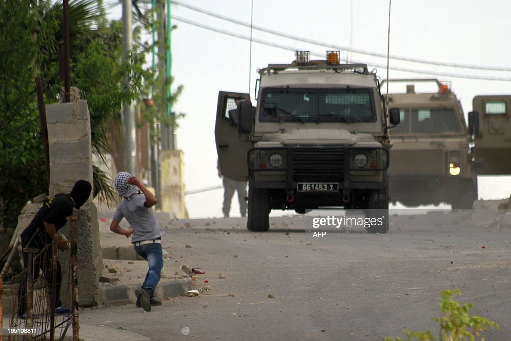 Palestinian protesters throw stones towards an Israeli army vehicle during clashes following a rally marking Land Day in the al-khader village near the West Bank town of Bethlehem on March 30, 2013. The annual demonstrations mark the deaths of six Arab Israeli protesters at the hands of Israeli police and troops during mass protests in 1976 against plans to confiscate Arab land in the northern Galilee region.