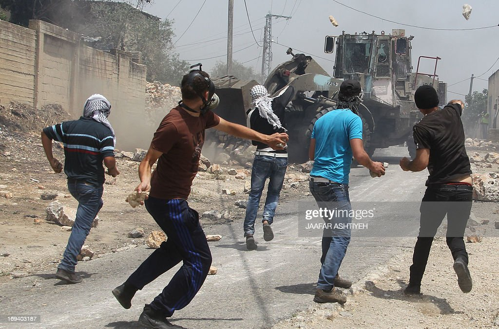 Palestinian protesters throw stones towards an Israeli bulldozer during clashes following a protest against the expropriation of Palestinian land by Israel on May 24, 2013 in the village of Kafr Qaddum, near the occupied West Bank city of Nablus.