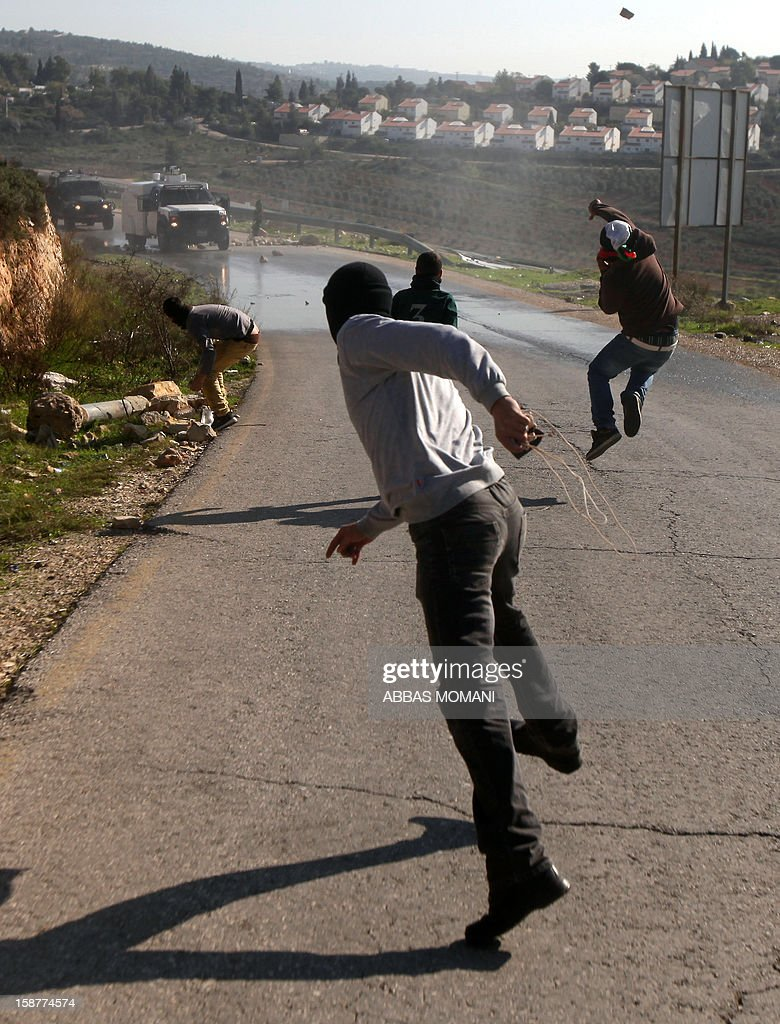 Palestinian protesters throw stones towards Israeli military vehicles during clashes that erupted following a march organised by residents of the West Bank village Nabi Saleh to protest against the expansion of Jewish settlements on Palestinian land on December 28, 2012.
