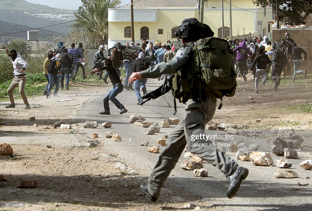 Palestinian protesters throw stones towards Israeli security forces during clashes following a protest against the expropriation of Palestinian land by Israel on February 15, 2013, in the village of Kafr Qaddum, near the occupied West Bank city of Nablus. AFP PHOTO/JAAFAR ASHTIYEH
