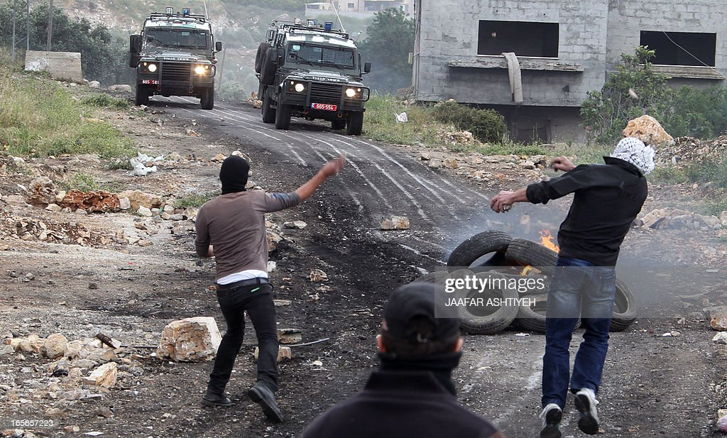 Palestinian protesters throw stones towards Israeli troops during clashes following a protest against the expropriation of Palestinian land by Israel in the village of Kfar Qaddum near Nablus in the occupied West Bank on April 5, 2013.