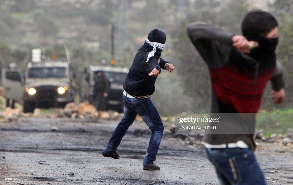 Palestinian protesters throw stones towards Israeli troops during clashes in the village of Kafr Qaddum near the West Bank city of Nablus on December 21, 2012 following a protest against the expropriation of Palestinian land by Israel. AFP PHOTO/JAAFAR ASHTIYEH