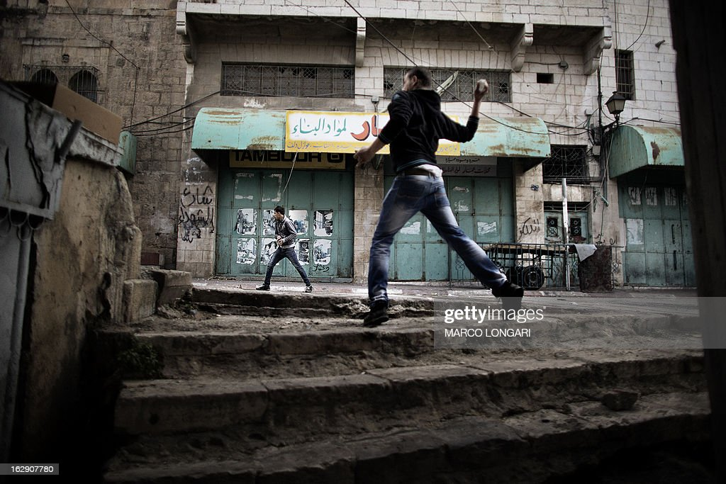 Palestinian protesters throw stones towards Israeli troops during clashes in the old city of Hebron on March 1, 2013 following a protest demanding the reopening of Shuhada Street, the one-time heart of the city. Flanked by a handful of Jewish settlement enclaves, the Shuhada Street was partially closed off in 1994 after local settler Baruch Goldstein opened fire on Muslim worshippers at the city's Al-Ibrahimi mosque, killing 29 of them. AFP PHOTO/MARCO LONGARI