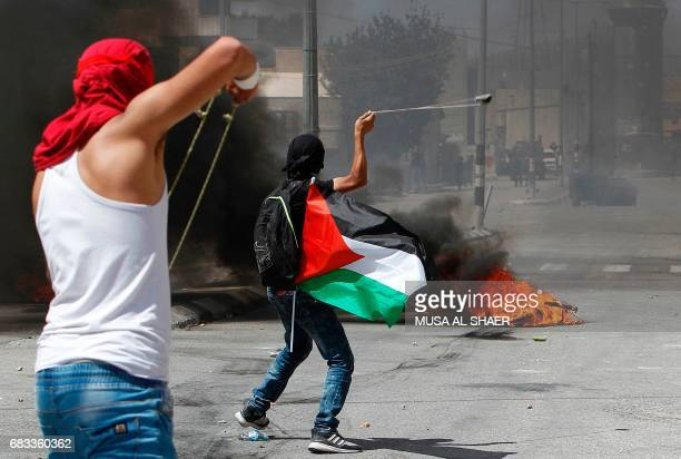 Palestinian protesters use a sling shot to throw stones towards Israeli security forces during clashes following a demonstration marking the 69th...
