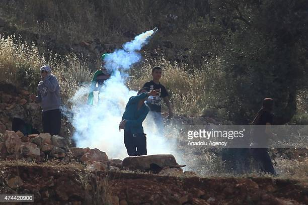 Palestinian protesters uses slingshot to throw stones during clashes with Israeli security forces after the demonstration staged to support...
