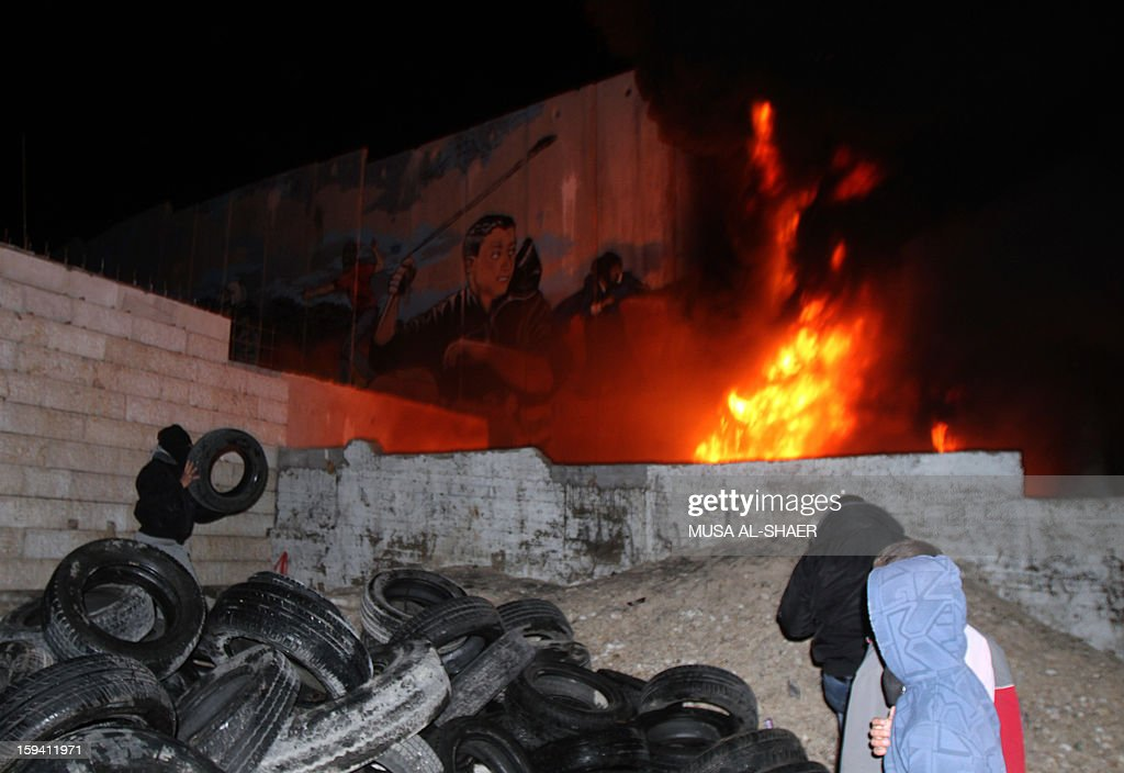 Palestinian protesters watch a burning pile of tires under an Israeli military observer tower along the controversial separation barrier during a protest in Aida Palestinian refugee camp near the West Bank city of Bethlehem on January 13, 2013. Earlier, some 500 Israeli police moved to evacuate the West Bank Palestinian protest camp of Bab al-Shams, a tent village activists set up on January 11, in the controversial E1 area outside Jerusalem, several kilometers from Bethlehem. AFP PHOTO/MUSA AL-SHAER