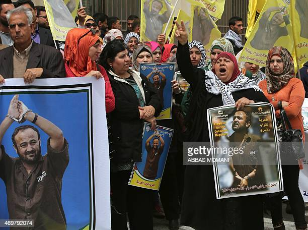 Palestinian protesters wave flags and placards bearing portraits of Fatah leader Marwan Barghuti during a march to mark the anniversary of his arrest...