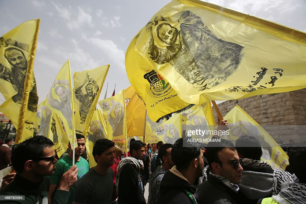 Palestinian protesters wave flags and placards bearing portraits of Fatah leader Marwan Barghuti, during a march to mark the anniversary of his arrest and demand his release from Israeli prison, in the West Bank city of Ramallah on April 15, 2015. Barghuti was sentenced to life imprisonment in 2002 for organizing anti-Israeli attacks during the Second Intifada in 2000