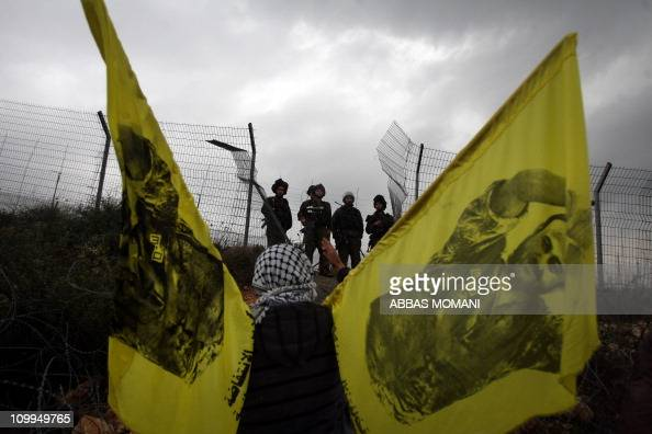Palestinian protesters wave flags with the image jailed Fatah leader Marwan Barghuti infront of Israeli soldiers during the weekly demonstration...