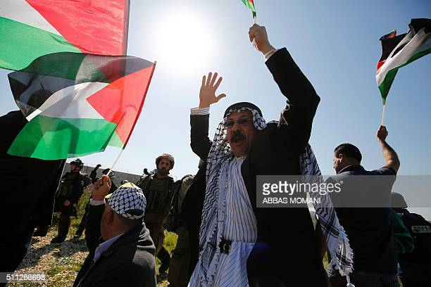 Palestinian protesters wave national flags next to Israeli security forces during clashes following a march on February 19 2016 in the West Bank...