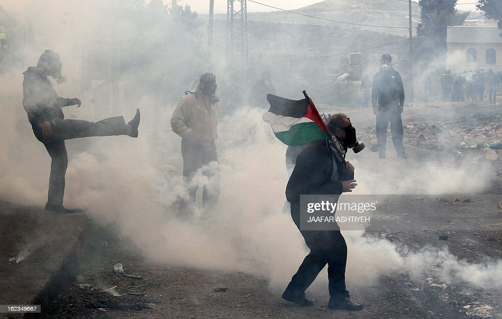 Palestinian protesters wearing gas masks stand amid a fog of tear gas fired by Israeli troops during clashes following a demonstration in support of Palestinian hunger-striking prisoners and against the expropriation of Palestinian land by Israel in the village of Kfar Qaddum near Nablus in the occupied West Bank on February 22, 2013. Palestinians demanding the release of hunger-striking prisoners clashed with Israelis in the West Bank and east Jerusalem, as three fasting inmates were taken to hospitals. AFP PHOTO/JAAFAR ASHTIYEH