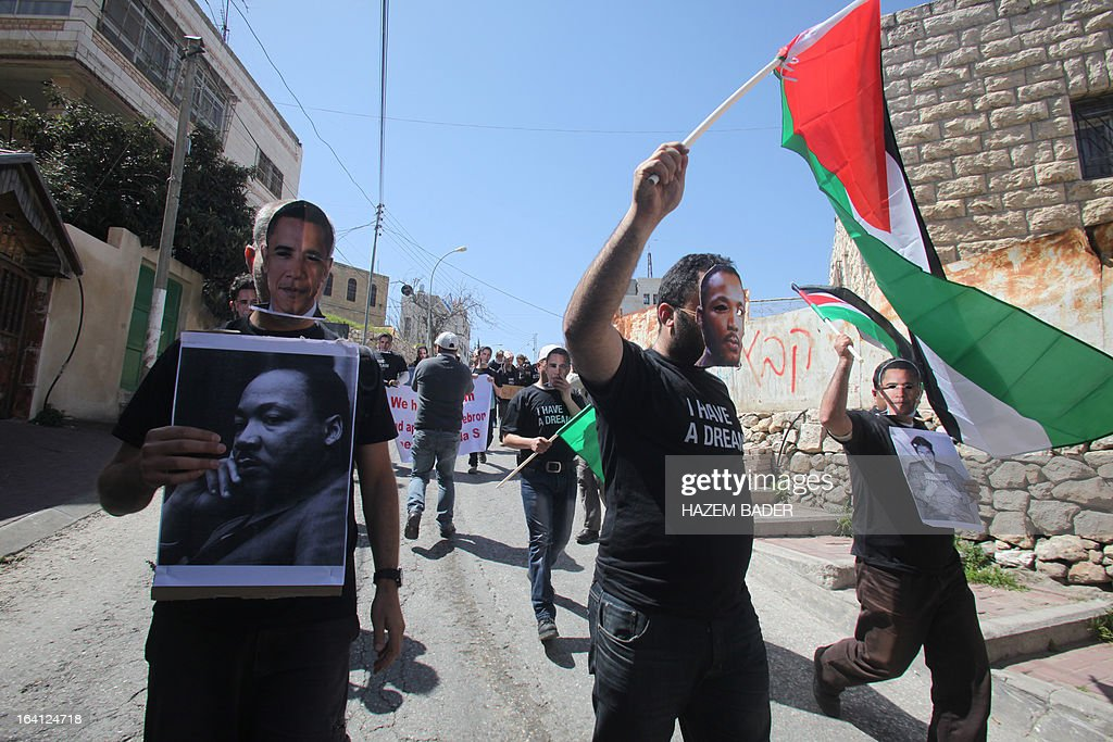 Palestinian protesters wearing masks of US President Barack Obama (L) and late American civil rights activist Martin Luther King (C), wave national flags during a protest in the divided West Bank city of Hebron on March 20 , 2013 against a visit by US President Barack Obama to the region. Obama said in his arrival statement in Tel Aviv that the US is proud to stand with Israel as its strongest ally and greatest friend.