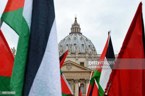 Palestinian protesting in solidarity with the people of the Gaza Strip wave Palestinian flags in front of St Peter's basilica during the weekly papal...