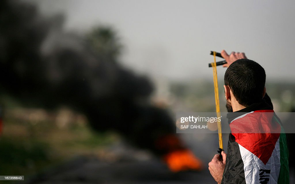 A Palestinian protestor aims his slingshot at Israeli police during clashes at the entrance of the Jalama checkpoint, near the West Bank city of Jenin, on February 22, 2013. Palestinians demanding the release of hunger-striking prisoners clashed with Israelis in the West Bank and east Jerusalem, as three fasting inmates were taken to hospitals.