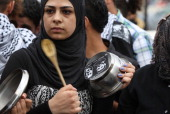 A Palestinian protestor bangs a wooden spoon on a pot covered in pictures of Palestinian prisoners Mahmoud alSarsak and Akram alRikhawi who are still...