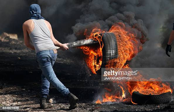 Palestinian protestor carries a burning car tire during clashes with Israeli security forces following a weekly demonstration against the...