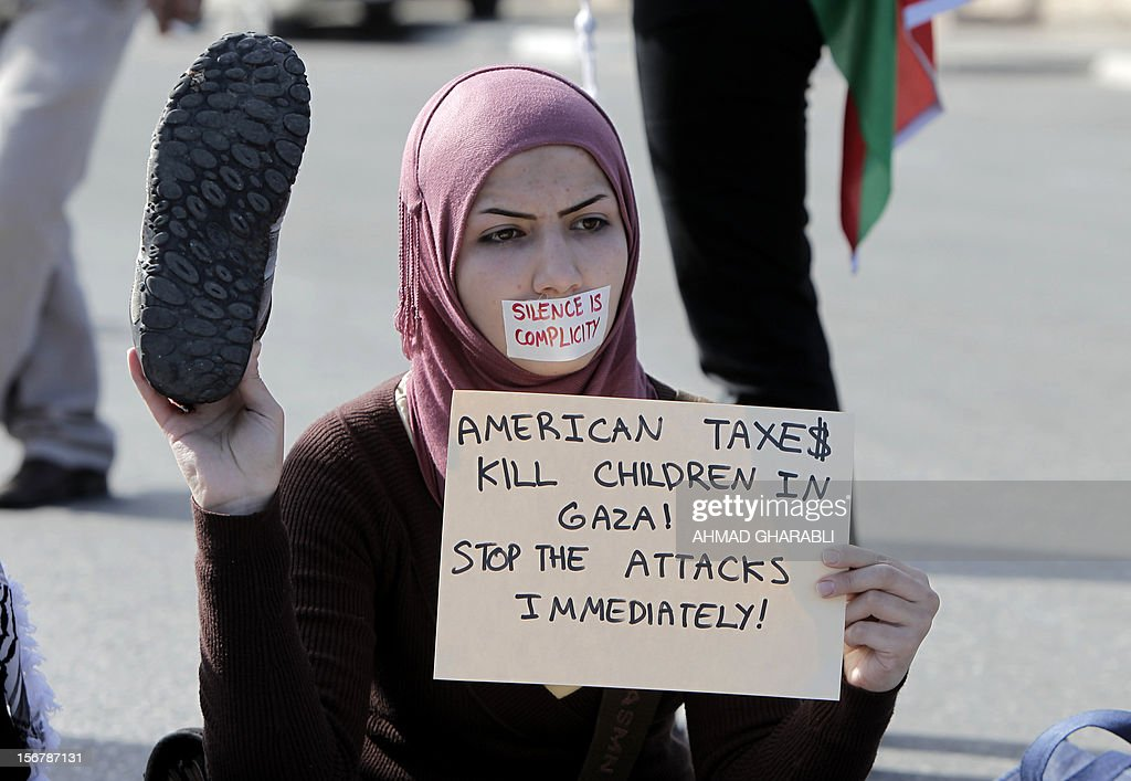 A Palestinian protestor carries a placard and a shoe during a demonstration against US Secretary of State Hillary Clinton's visit in the West Bank city of Ramallah on November 21, 2012. US Secretary of State Hillary Clinton expressed 'rock solid' support for Israel's security while calling for a de-escalation of the conflict in Gaza where fighting entered its eighth day, despite signs of an emerging truce.