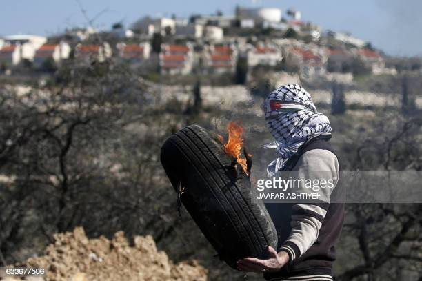 A Palestinian protestor carries burning car tire during clashes with Israeli security forces following a weekly demonstration against the...