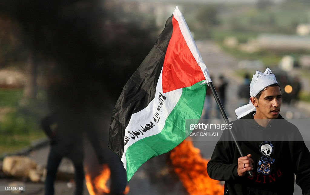 A Palestinian protestor carries the national flag during clashes with Israeli police at the entrance of the Jalama checkpoint, near the West Bank city of Jenin, on February 22, 2013. Palestinians demanding the release of hunger-striking prisoners clashed with Israelis in the West Bank and east Jerusalem, as three fasting inmates were taken to hospitals.