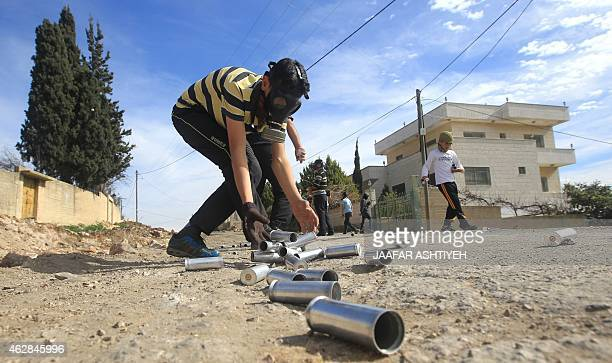 A Palestinian protestor collects empty tear gas canisters during clashes following a demonstration against the expropriation of Palestinian land by...