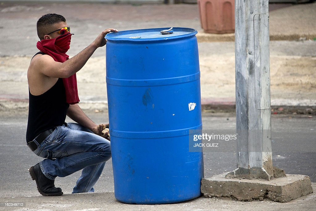 A Palestinian protestor hides behind a barrel to protect himself from rubber bullets fired by Israeli security forces during clashes next to Ofer prison, near the West Bank city of Ramallah, following a demonstration in support of Palestinian detainees on hunger strike in Israeli prisons on February 22, 2013. Palestinians demanding the release of hunger-striking prisoners clashed with Israelis in the West Bank and east Jerusalem, as three fasting inmates were taken to hospitals. AFP PHOTO / JACK GUEZ
