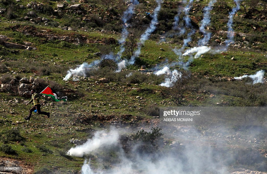 A Palestinian protestor, holding his national flag, runs for cover from tear gas fired by Israeli soldiers during clashes following a demonstration organised by residents of the West Bank village Nabi Saleh to protest against the expansion of Jewish settlements on Palestinian land on February 8, 2013. AFP PHOTO/ABBAS MOMANI